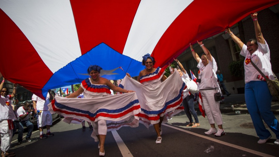 Women run under a Puerto Rican flag before the National Puerto Rican Day Parade on Fifth Avenue in Manhattan
